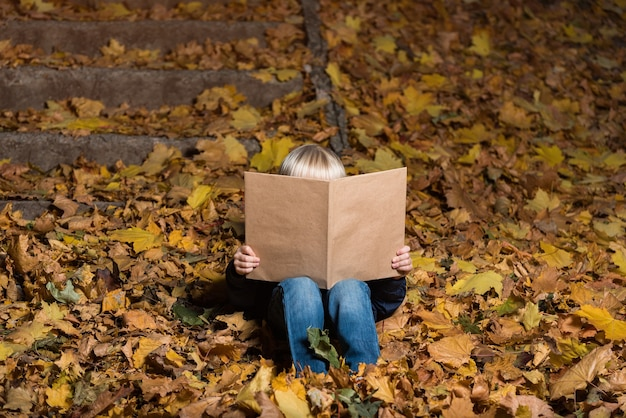 Little boy holding large book in hands and sitting on fallen autumn leaves. child loves to read. Premium Photo