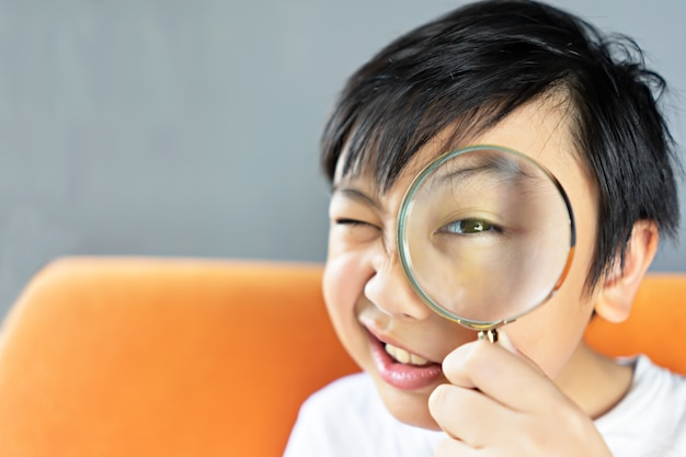 Little boy holding magnifying glass Premium Photo