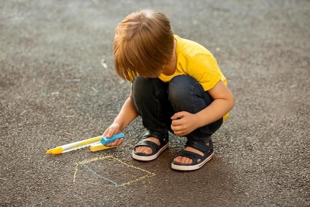 Маленький мальчик в парке, рисование мелом Бесплатные Фотографии