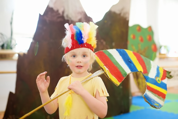 Little boy involved in performance children's theatre studio in the role of the american indian. Premium Photo