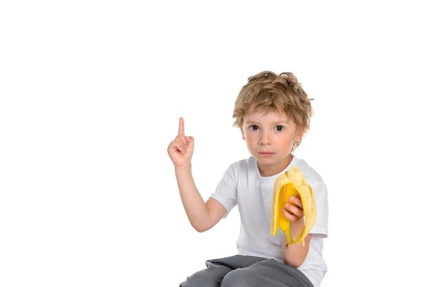 Маленький мальчик ест банан, серьезно смотрит и показывает вверх Premium Фотографии