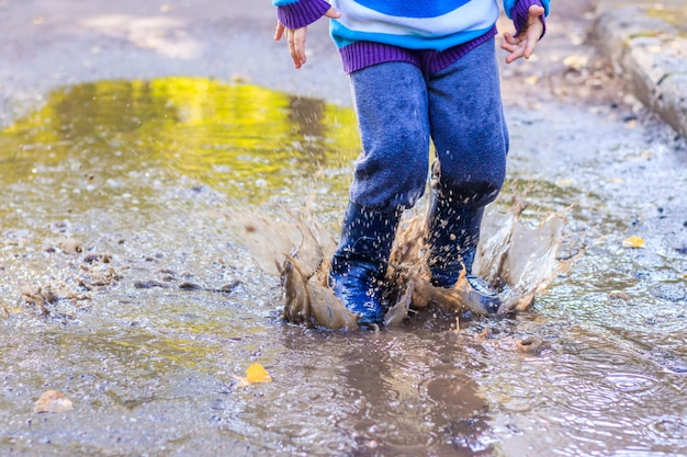 A little boy is jumping in a puddle. Premium Photo