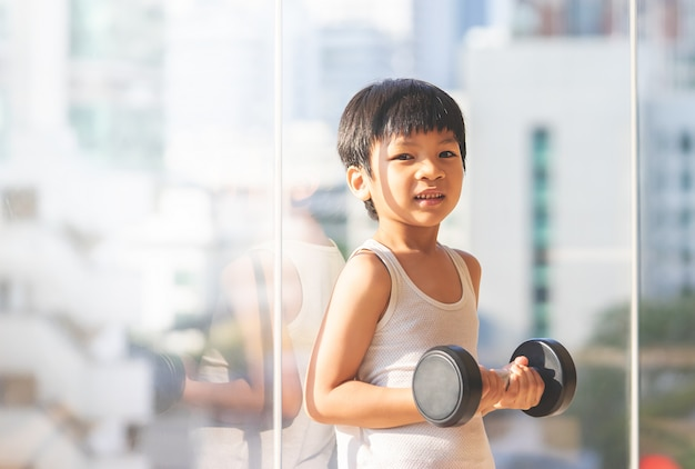Little boy is working out with dumbbell by the windows city. Premium Photo