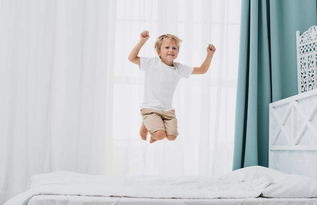 Little boy jumping while looking at the camera Free Photo