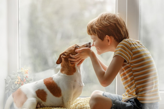 Little boy kisses the dog in nose on the window. Premium Photo