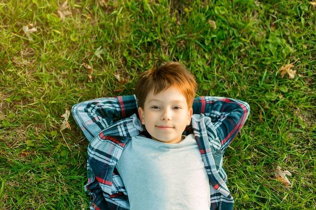 Маленький мальчик лежит на зеленой траве Premium Фотографии