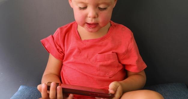 Little boy looking enthusiastically screen phone sitting sofa Premium Photo