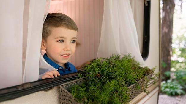 彼のキャラバンの窓の外を見て少年 無料写真