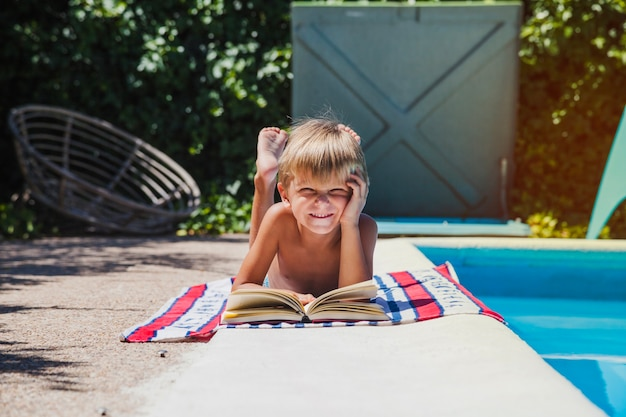 Little boy lying on towel near pool Free Photo