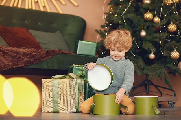 Little boy near christmas tree in a gray sweater Free Photo