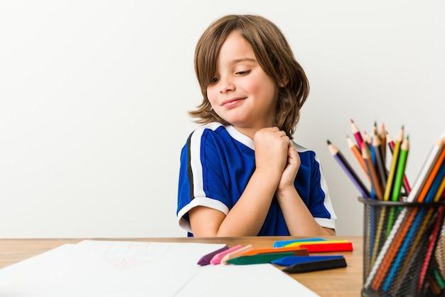 絵画と彼の机の上の宿題をやっている少年は怖いと恐れていた。 Premium写真