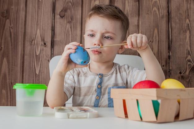Маленький мальчик красит красочные пасхальные яйца на деревянной стене Premium Фотографии