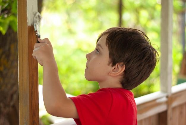 Маленький мальчик рисует деревянное здание кистью Premium Фотографии