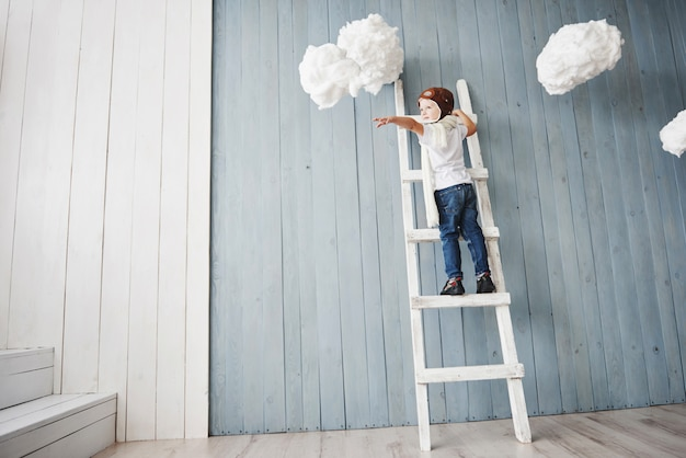 Little boy in pilot hat standing on the ladder in the . reach to heaven. touch the clouds Premium Photo