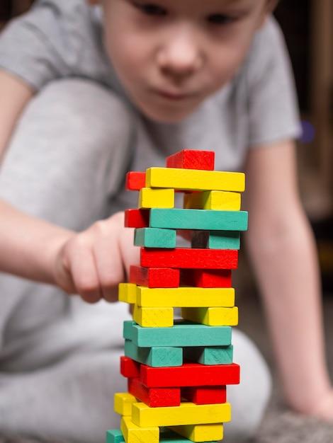 Маленький мальчик с красочной деревянной башней игры Бесплатные Фотографии