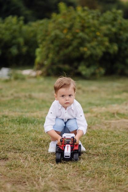 小さな男の子は芝生の上のおもちゃの車で遊ぶ 無料写真