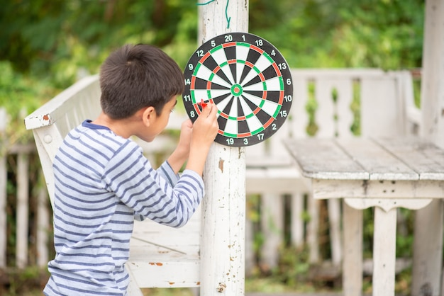Little boy playing darts board family outdoor activity Premium Photo