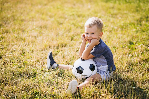 Little boy playing football at the field Free Photo