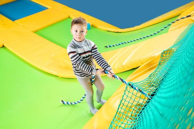 Маленький мальчик играет в батуте центр прыжки и скалолазание с веревкой Premium Фотографии