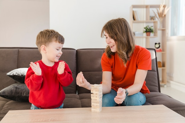 Little boy playing janga with his mom Free Photo
