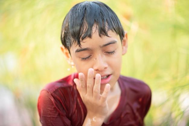 Маленький мальчик, играя фонтанчик капли воды под тканью и зонтик Premium Фотографии