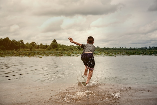 Little boy playing water in the river Premium Photo