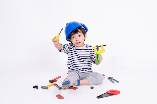Little boy playing with construction equipment on white Free Photo