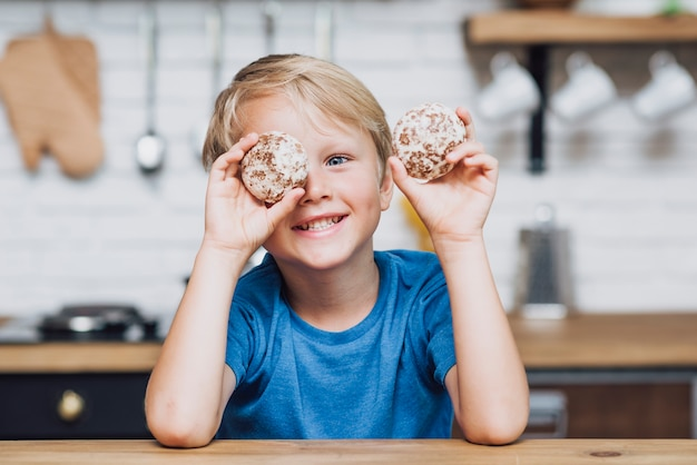 Little boy playing with cookies Free Photo