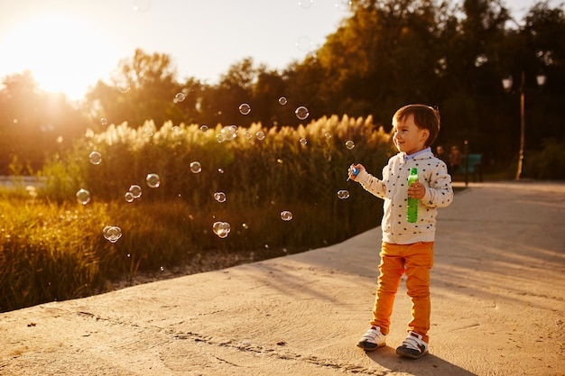 Little boy playing with soap bubbles Free Photo