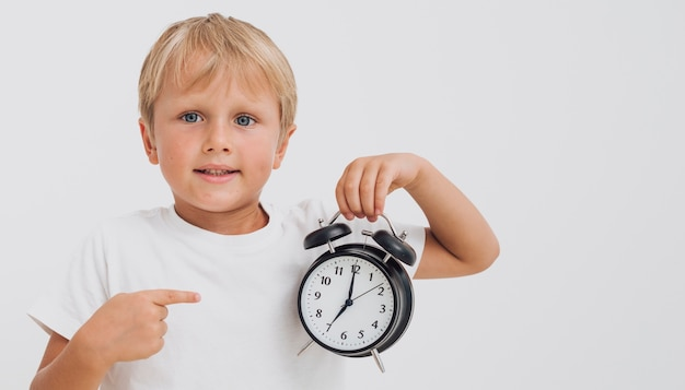 Little boy pointing at a clock Free Photo