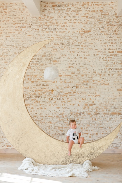 Little boy posing on big moon toy with loft brick wall background Free Photo