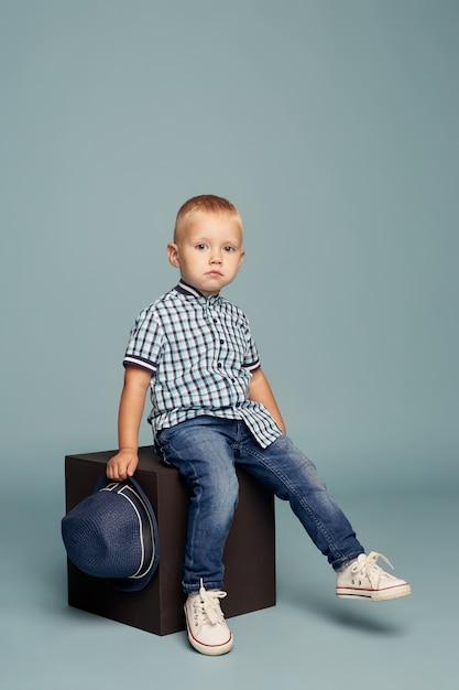 Маленький мальчик позирует, веселые эмоции мальчика модель. красивый ребенок играет прыгать и морщиться, сидя на ярком кубе. , Premium Фотографии