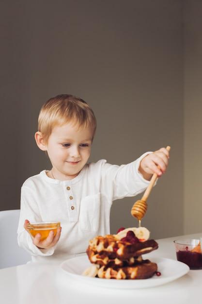 Little boy putting honey on waffle Free Photo