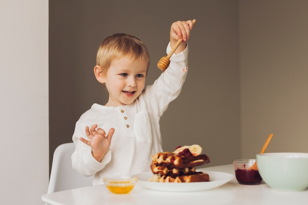 Little boy putting honey on waffle Free Photo
