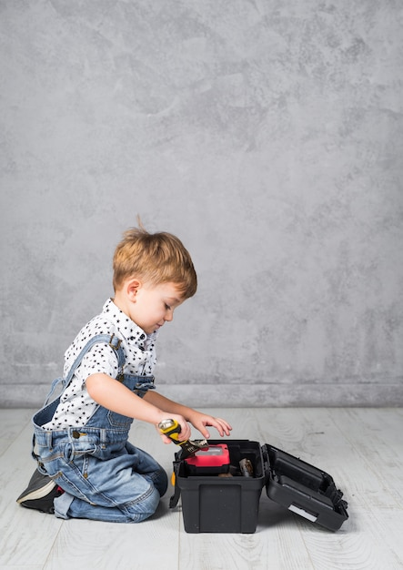 Little boy putting spanner in tool box Free Photo