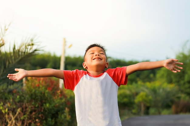 Little boy raising hands up over and looking to sunset on sky. Premium Photo