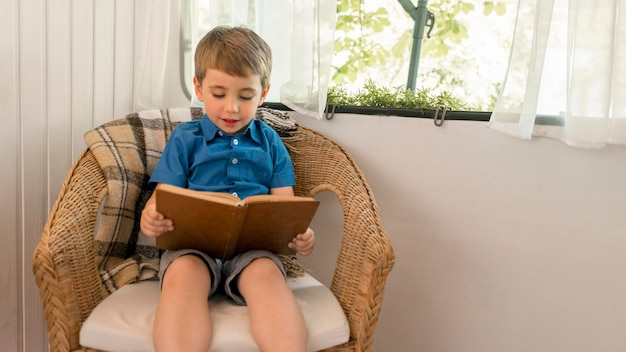 キャラバンの肘掛け椅子に座って本を読んで小さな男の子 無料写真