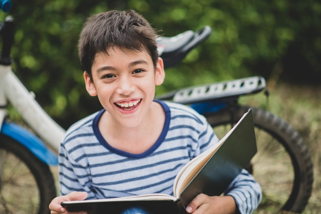 Little boy reading book sitting with bicycle in the park Premium Photo
