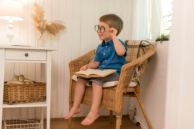 Free Photo   Little boy reading while sitting in an armchair