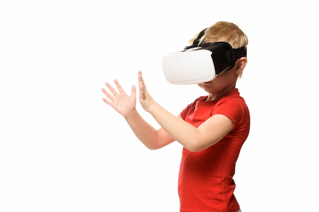 Little boy in a red shirt is experiencing virtual reality holding hands in front of him. isolate on white Premium Photo