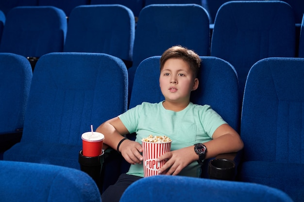Little boy resting and enjoying action movie in cinema Free Photo