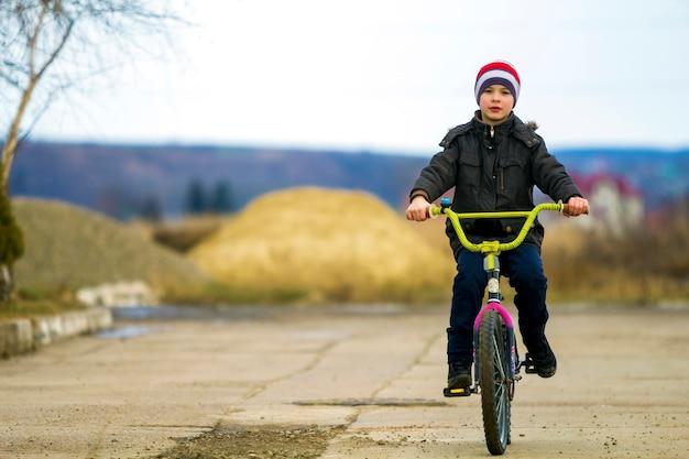 Маленький мальчик, езда на велосипеде в парке на открытом воздухе. Premium Фотографии
