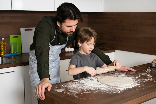 Little boy rolling dough at home Free Photo
