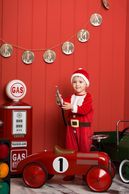 Little boy in santa claus costume rides a toy red car. Premium Photo