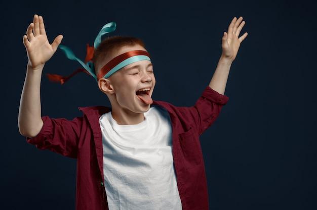 小さな男の子は、風の強いスタジオで悲鳴を上げます。子供と風、暗い背景、子供の感情に分離された子供 Premium写真