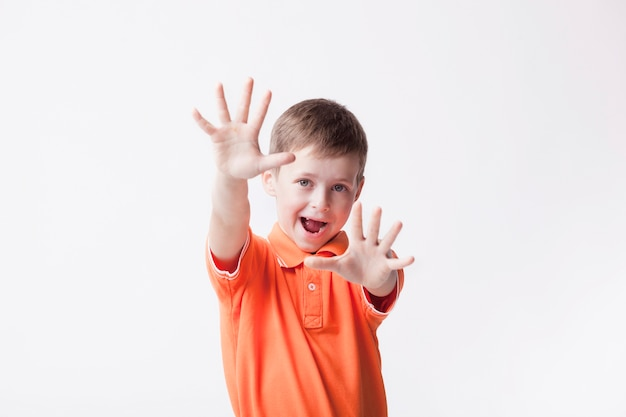 Little boy showing stop gesture with mouth open over white background Free Photo