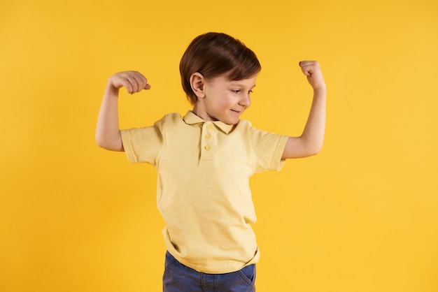 Little boy shows biceps isolated on yellow Premium Photo