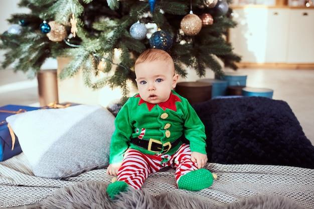 小さな男の子はクリスマスツリーに座っています 無料写真