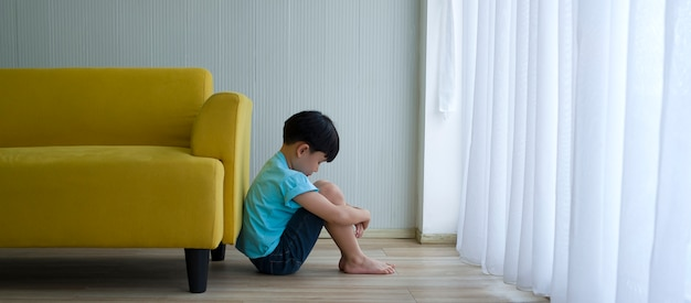 Little boy sitting beside yellow sofa at home. child autism. Premium Photo
