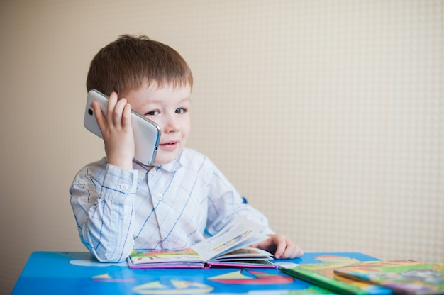 Little boy sitting at desk and talking on the phone Premium Photo